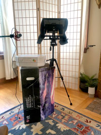 Photograph of a camera and teleprompter on a tripod stand in a living room, next to a microphone stand, in front of a transparent screen.