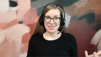 Smiling woman with headset and glasses in front of a multicolor background